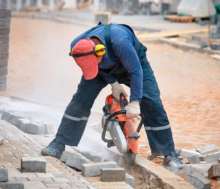 Man cutting through concrete while wearing PE equipment - Noise management on construction site